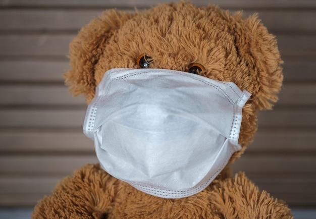 Teddybeer in een medisch masker zit thuis