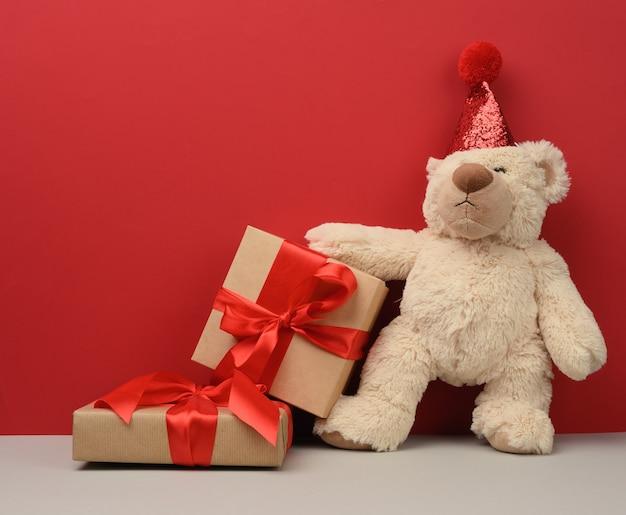 Teddybeer in een rode feestelijke hoed houdt een roze vel papier vast