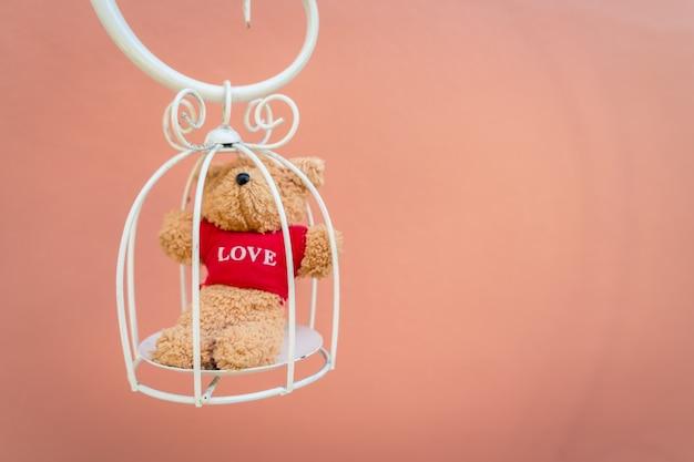 Teddybeer in een witte kooi