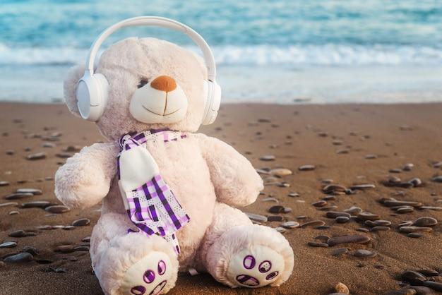 Teddybeer in koptelefoon aan de zeekust in de middag