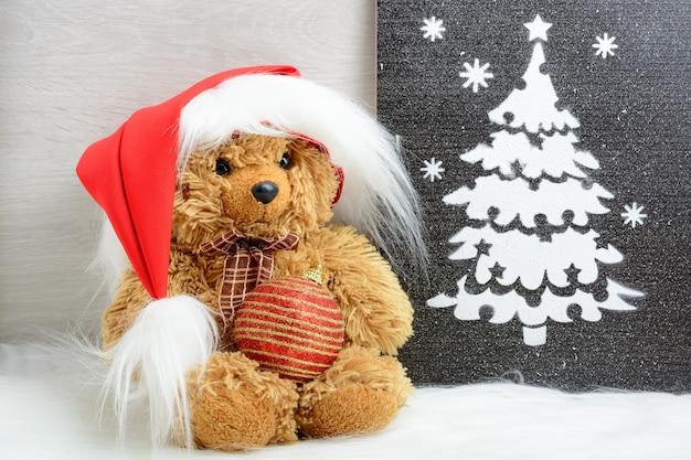 Teddybeer in santahoed dichtbij kerstboombeeld