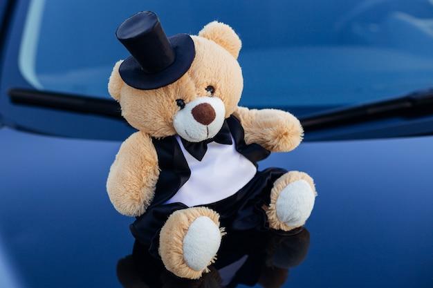 Teddybeer in smoking draagt een vlinderdas en een hoed