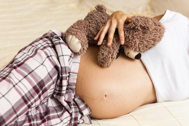 Teddybeer knuffelen buik van zwangere vrouw