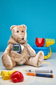 Teddybeer met een glucometer en verspreid kinderspeelgoed en insulinepennen op een blauw en wit