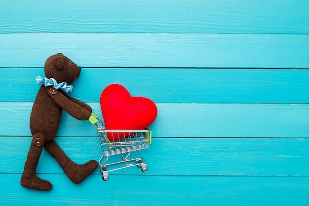 Teddybeer met een hart in handen op blauwe achtergrond