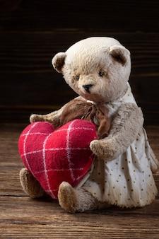Teddybeer met een rood hart op een houten tafel