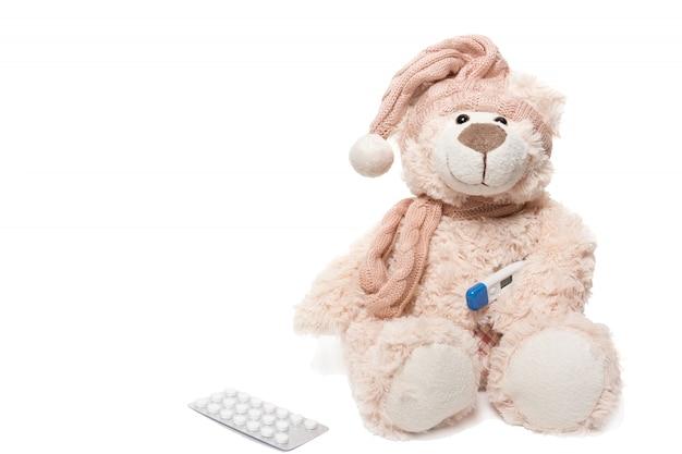 Teddybeer met een thermometer en pillen