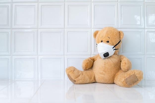 Teddybeer met gezichtsmasker op wit oppervlak.