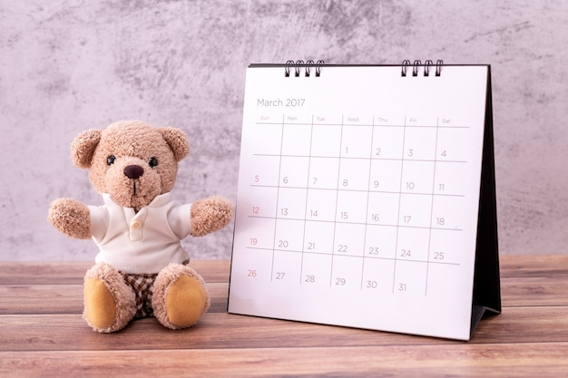 Teddybeer met kalender op houten lijst.