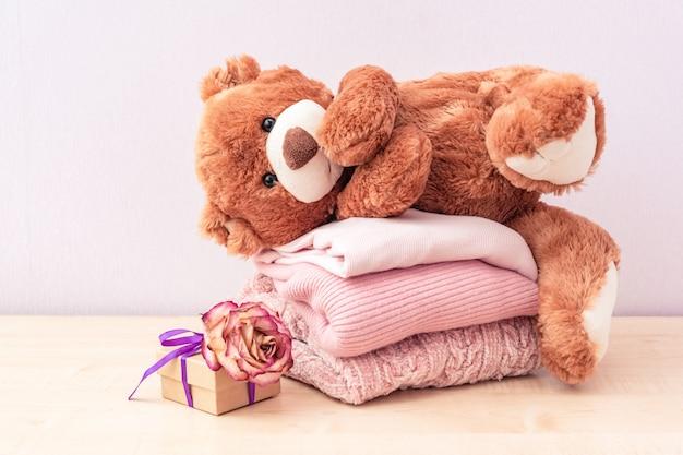 Teddybeer speelgoed en stapel gebreide dameskleding, warme truien, een jasje, een blouse in pastelroze kleuren