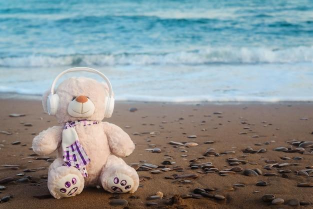 Teddybeer speelgoed in koptelefoon bij de zee