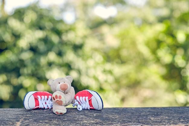 Teddybeer verkleedt rode schoenen op houten stoel in natuurlijke ruimte