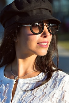 Teder buitenportret van sensuele brunette dame poseren op straat, zachte kleuren, witte jurk, elegant glamourmodel.