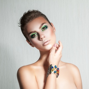 Teder meisje met mooie make-up en kort haar studio opname grijze achtergrond