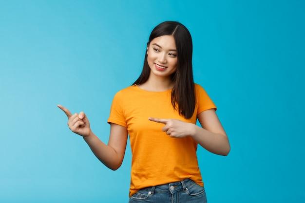 Teder mooi aziatisch meisje met donker kapsel kijkt nieuwsgierig naar links, geïnteresseerd in nieuw product in de winkel, staat geamuseerd op een blauwe achtergrond, vermaakt, observeert tentoonstelling, draagt geel t-shirt.