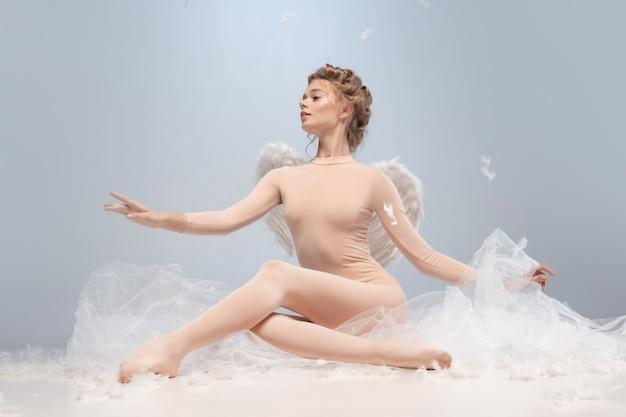Teder portret van jonge en sierlijke ballerina dansen geïsoleerd op een witte grijze background