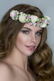 Teder schoonheidsportret van bruid met bloemenkroon in haar
