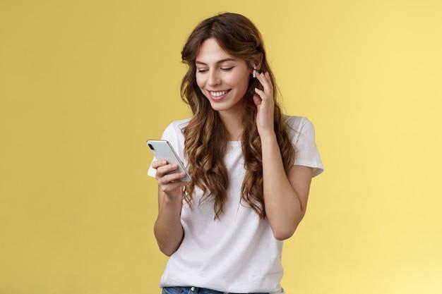 Teder vrouwelijk krullend haar vrouw wit t-shirt aanraking draadloos oordopjes zetten oortelefoon oor glimlachen tevreden kijken smartphone scherm kiezen lied wil luisteren muziek zoeken juiste spoor gele achtergrond