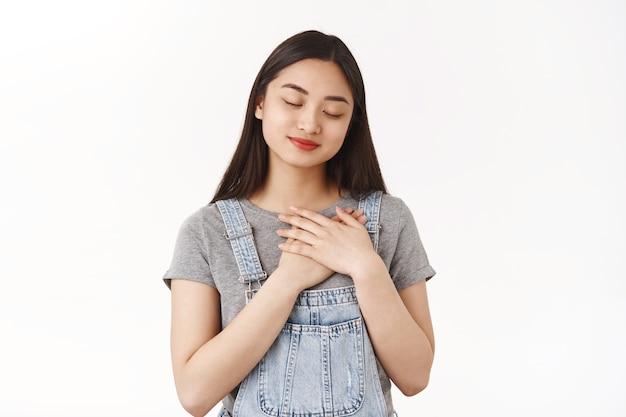 Teder zorgzaam lieflijk romantisch aziatisch jong meisje denken minnaar sluiten ogen beeldvorming koesteren geheugen glimlachen opgetogen hand in hand houden hart uiten sympathie tederheid diepe oprechte gevoelens
