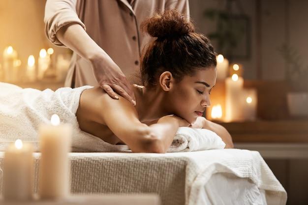 Tedere afrikaanse vrouw die genietend van massage met gesloten ogen in kuuroordtoevlucht glimlachen.