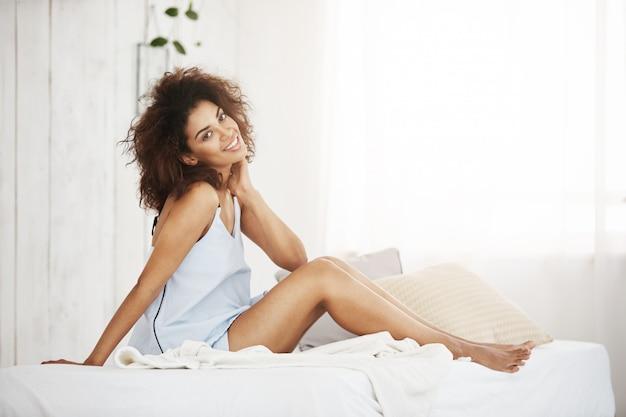 Tedere afrikaanse vrouw in nachtkledingzitting op bed die thuis glimlachen.