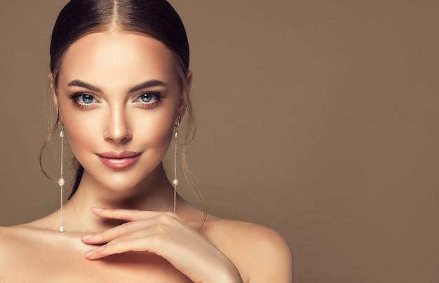 Tedere blik op de kijker en elegant gebaar portret van jonge mooie vrouw in lange oorbellen
