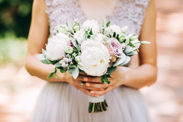 Tedere bruid die een huwelijksboeket houdt. bruid op aard met een boeket van pioenen.