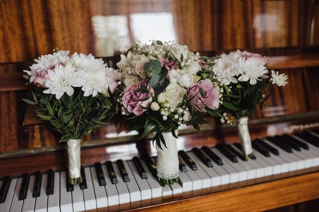 Tedere bruidsboeketten voor bruid en bruidsmeisjes op de ouderwetse piano