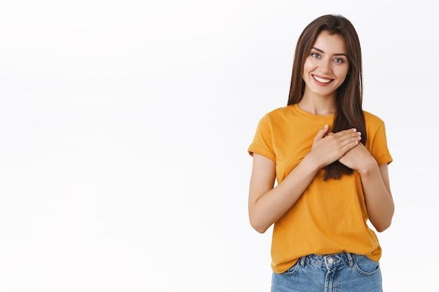 Tedere, charmante blanke vrouw in geel t-shirt, handen tegen het hart gedrukt, relatie en liefde koesteren, vreugdevol glimlachen, dromerige camera, staande blije witte achtergrond
