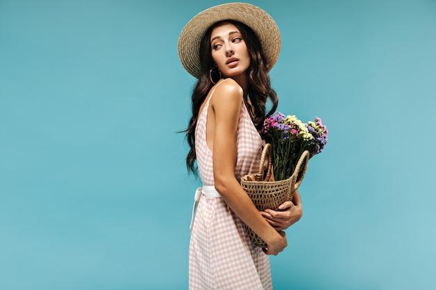 Tedere charmante vrouw met zwart golvend haar en oorbellen in stijlvolle hoed en zomerjurk poseren met bloemen op blauwe muur