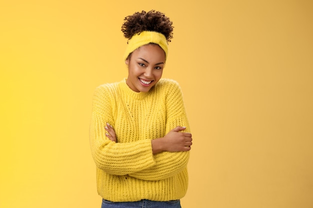 Tedere delicate jonge afro-amerikaanse vrolijke vriendin krullend kapsel hoofdband trui knuffelen zichzelf omarmen graag lachende camera voelt zacht comfortabel, staande gele achtergrond warm.