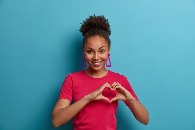 Tedere donkere huid jonge vrouw maakt hartgebaar, toont liefde, genegenheid, passie, draagt casual roze t-shirt en oorbellen, geïsoleerd op blauwe muur. lichaamstaal, romantiek, gevoelens concept