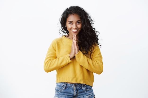 Tedere en schattige jonge vrouw met krullend haar in gele trui, spijkerbroek die om gunst vraagt, bedankt voor hulp, handpalmen tegen elkaar drukt in gebed, vrolijk glimlacht, staande witte muur gelukkig