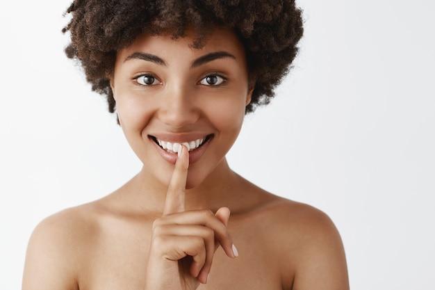 Tedere en vrouwelijke donkere vrouw met schone en zachte huid, glimlachend met intrigerende uitdrukking, stil teken met wijsvinger over de mond tonen