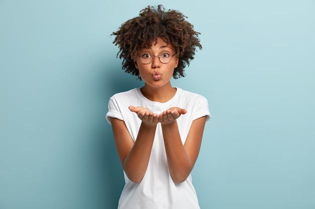 Tedere gevoelens. mooie krullende vrouw met afro-kapsel, vouwt de lippen en stuurt luchtkus, geeft mwah, strekt de handpalmen uit, draagt een transparante bril voor zichtcorrectie, geïsoleerd over blauwe muur