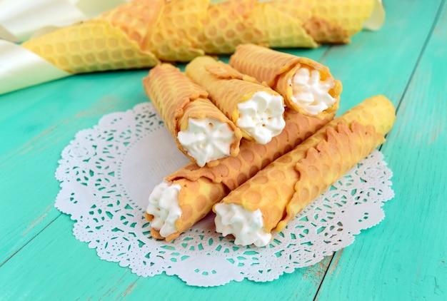 Tedere honingwafeltjes in de vorm van buizen, gevuld met luchtcrème op wit kanten servet. detailopname.