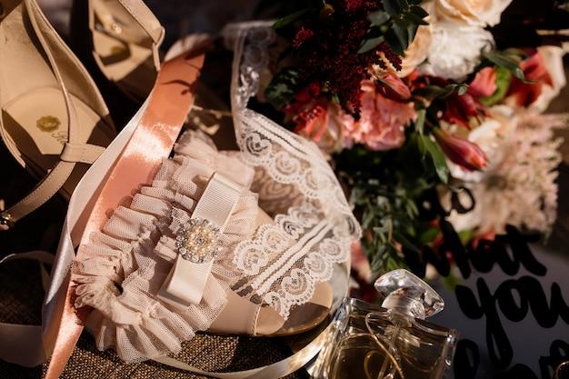 Tedere huwelijkstoebehoren voor bruid en huwelijksboeket op de zonnige dag