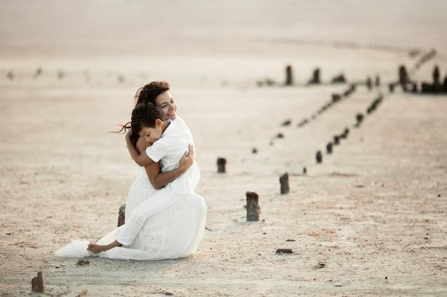 Tedere knuffels van moeder en een kind op het zand voor zonsondergang