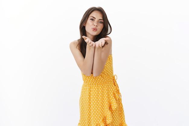 Tedere kokette mooie brunette vrouw in zomer gele jurk, wind kus blazen, handpalmen in de buurt van pruillip lippen houden om muah camera te sturen, flirterig en dwaas kijken witte muur romantische verleidelijke stemming