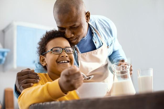 Tedere liefde. zorgzame jonge vader knuffelen zijn zoontje bij het ontbijt terwijl hij melk in zijn kom met granen gieten