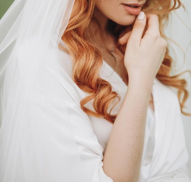 Tedere lippen en huid van charmante bruid met rood krullend haar