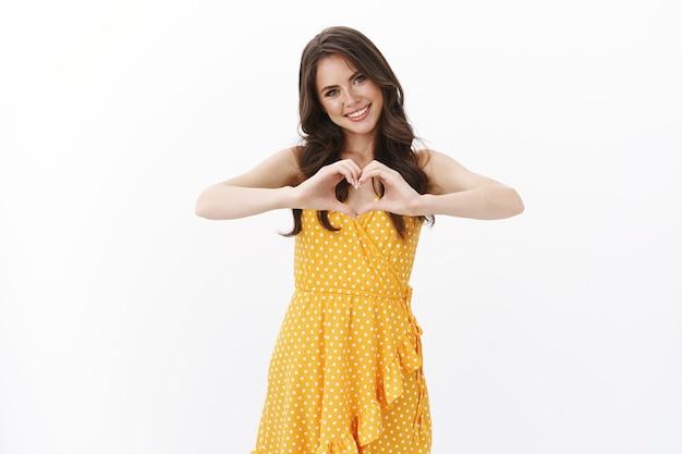 Tedere mooie mooie jonge vriendin in stijlvolle gele jurk, hartteken tonen en glimlachend zorgzaam, zeg dat ik van je hou, positiviteitsgeluk en romantische gevoelens uitdrukken, witte muur staan