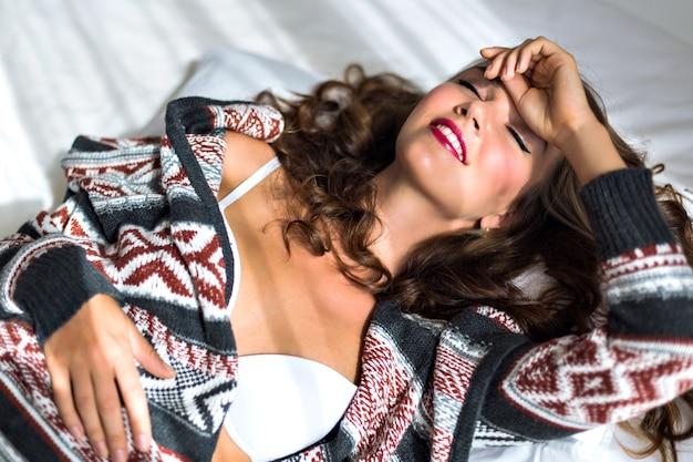 Tedere ochtend close-up portret van verleidelijke sensuele vrouw lag op haar bed, ontspannend en geniet van de ochtendtijd, het dragen van beha en gezellige wollen trui, zacht zonnig licht.