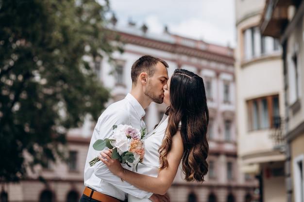 Tedere omhelzingen van een huwelijkspaar die rond een oude europese stad lopen