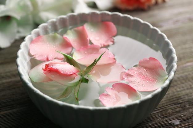 Tedere roze roos en bloemblaadjes in een kom water op houten tafel