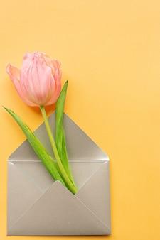 Tedere roze tulp in elegante grijze envelop aan linkerkant van pastelkleur gele achtergrond. kopieer ruimte. plaats voor tekst. concept van internationale vrouwendag, moederdag, pasen. valentijnsdag liefdesdag.