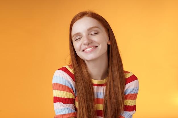 Tedere sensuele dromerige schattig roodharige vrouwelijk meisje droomt van smakelijke plak pizza sluit ogen glimlachend verrukt kwijlen staande gefascineerd gebiologeerd herinnerend aan mooi moment, oranje achtergrond.