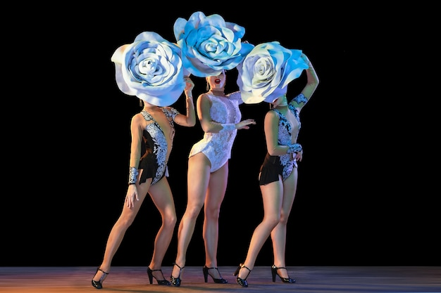Tedere tuin. jonge danseressen met enorme bloemenhoeden in neonlicht op zwarte muur.
