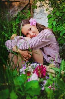 Tedere vrouw die in grasrijk struikgewas rust met een mooi boeket van pioenen en wilde bloemen