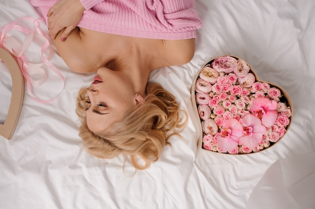 Tedere vrouw met roze overhemd dat op het bed dichtbij de doos van de hartvorm van roze gekleurde bloemen ligt